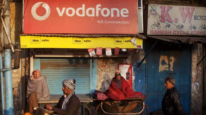 An Indian fruit vendor waits for customers in front of a mobile phone shop in New Delhi, India, Tuesday, Jan. 24, 2012. India's central bank said growth will slow to 7 percent this fiscal year, but left interest rates unchanged Tuesday as it struggles to balance a toxic mix of high inflation and a flagging economy. (AP Photo/Kevin Frayer)