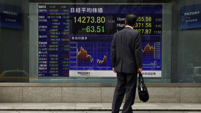 A man looks at an electronic stock indicator outside a securities firm in Tokyo, Thursday, Nov. 7, 2013. Asian stock markets were mostly weaker Thursday, with a cautious mood prevailing ahead of key U.S. data that will provide further clues on when the Federal Reserve will cut monetary stimulus. Japan's Nikkei 225 shed 0.7 percent to 14,238.95. (AP Photo/Junji Kurokawa)