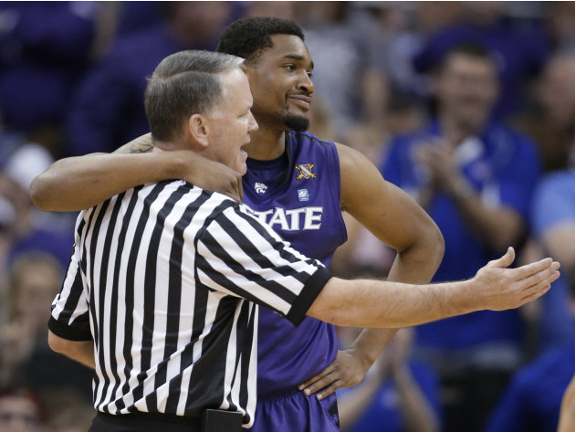 Kansas State guard Shane Southwell hugs referee Mike Stuart after a foul call during the first half against Kansas in an NCAA college basketball game for the Big 12 men's tournament title, Saturday, M