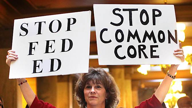 In this Jan. 16, 2013 file photo, concerned grandparent Sue Lile, of Carmel, Ind., shows her opposition to Common Core standards during a rally at the State House rotunda in Indianapolis. Some states are pushing back against the new set of uniform benchmarks for reading, writing and math that replace a hodgepodge of of goals that had varied wildly from state to state and are being widely implemented this school year in most states. (AP Photo/The Star, Frank Espich)