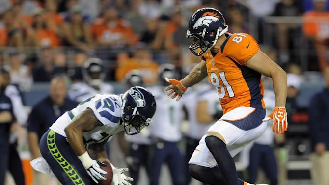 Seattle Seahawks defensive back Jeron Johnson (32) intercepts a pass intended for Denver Broncos tight end Joel Dreessen (81) in the first half of an NFL football preseason game on Saturday, Aug. 18, 2012, in Denver. (AP Photo/Jack Dempsey)