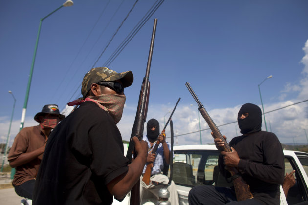 In this photo taken Friday Jan. 18, 2013, masked and armed men sit in the back of a pick-up truck at the entrance to the town of Ayutla, Mexico. Hundreds of men in the southern Mexico state of Guerrero have taken up arms to defend their villages against drug gangs, a vigilante movement born of frustration at extortion, killings and kidnappings in a region wracked by violence. (AP Photo/Dario Lopez-Mills)