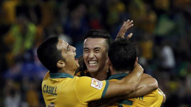 Australia's Jason Davidson celebrates with teammates Tim Cahill and Mark Milligan after scoring a goal against UAE during their Asian Cup semi-final soccer match at the Newcastle Stadium in Newcastle
