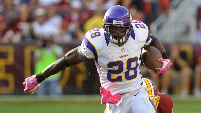 Minnesota Vikings running back Adrian Peterson (28) is hit by Washington Redskins linebacker Perry Riley (56) during the first half of an NFL football game, Sunday, Oct. 14, 2012, in Landover, Md. (AP Photo/Richard Lipski)