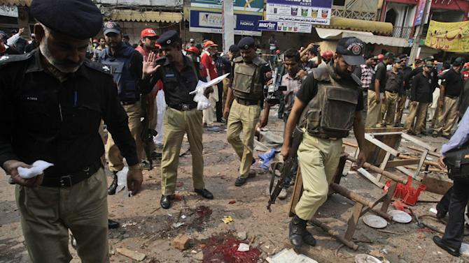 Pakistani police officers check the site of a deadly explosion in a busy market in Lahore, Pakistan, Thursday, Oct. 10, 2013. Police official, Raj Tahir, says the bomb, which was planted in a restaurant in the market and which went off on Thursday also wounded many people. (AP Photo/K.M. Chaudary)