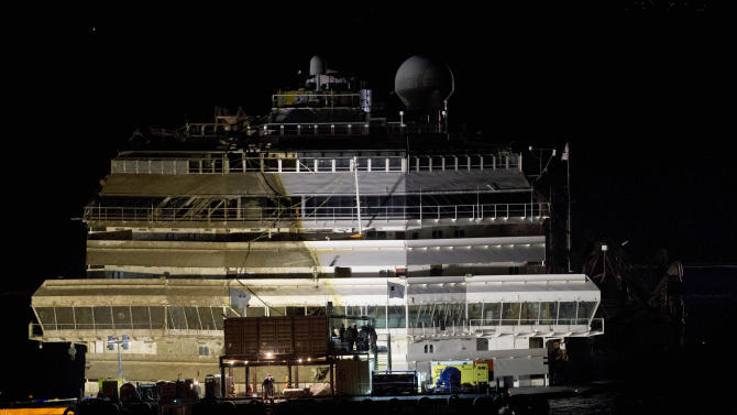 """The Costa Concordia rests upright on the Tuscan Island of Giglio, Italy, early Tuesday morning, Sept. 17, 2013. The crippled cruise ship was pulled completely upright early Tuesday after a complicated, 19-hour operation to wrench it from its side where it capsized last year off Tuscany, with officials declaring it a """"perfect"""" end to a daring and unprecedented engineering feat. (AP Photo/Andrew Medichini)"""
