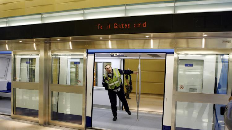 FILE - In this Jan. 25, 2010 file photo, an airport worker looks out of the car and through the open doorway of the glass security barrier at Washington Dulles International Airport in Washington. New York City transit officials are considering similar safety barriers between passenger platforms and trains after two people were pushed and a third fell to their deaths on the tracks since early December 2012. (AP Photo/Jose Luis Magana, File)