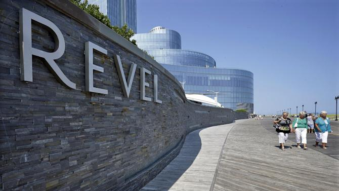 In this Wednesday July 23, 2014 photograph, People walk past the Revel Casino Hotel in Atlantic City, N.J. The Revel Casino Hotel will close its doors on Sept. 10, 2014 after failing to find a buyer in bankruptcy court, company officials announced Tuesday, Aug. 12, 2014. (AP Photo/Mel Evans)