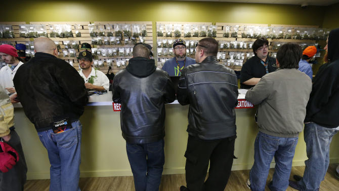 "Employees help customers at the crowded sales counter inside Medicine Man marijuana retail store, which opened as a legal recreational retail outlet in Denver on Wednesday Jan. 1, 2014. Colorado began retail marijuana sales on Jan. 1, a day some are calling ""Green Wednesday."" (AP Photo/Brennan Linsley)"