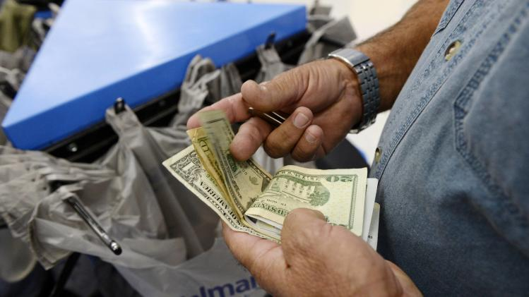 A customer counts his cash at the checkout lane of a Walmart store in the Porter Ranch section of Los Angeles