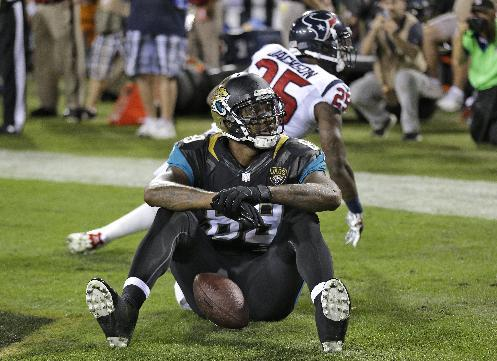 Jacksonville Jaguars tight end Marcedes Lewis (89) reacts after catching a one-yard touchdown pass in front of Houston Texans cornerback Kareem Jackson (25) during the first quarter of an NFL football game Thursday, Dec. 5, 2013, in Jacksonville, Fla