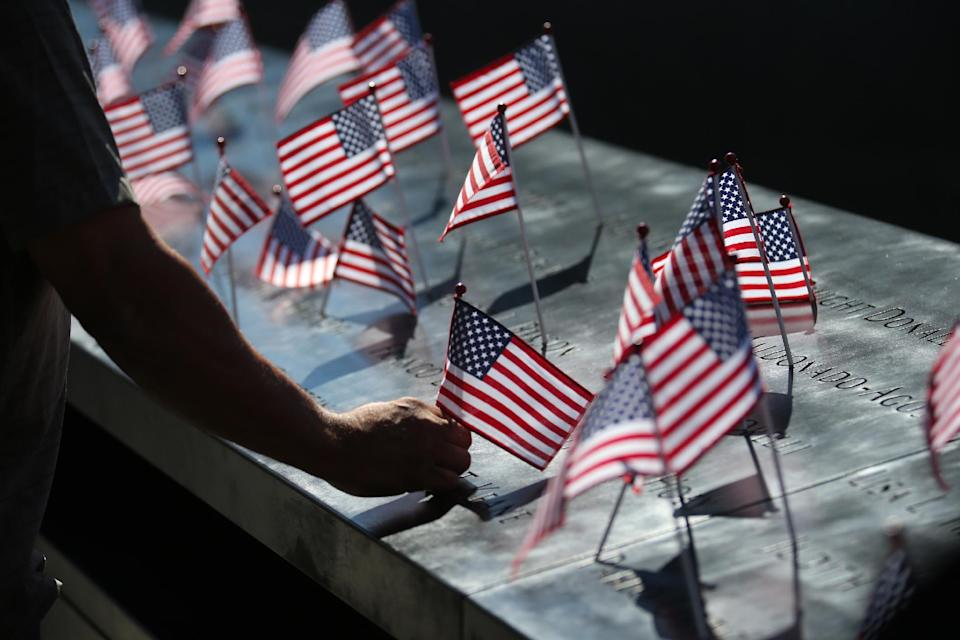 A man fixes an American flag that was fallen from the position during a ceremony marking the 11th anniversary of the Sept. 11 terrorist attacks at the National September 11 Memorial at the World Trade Center site in New York, Tuesday, Sept. 11, 2012. (AP Photo/The New York Times, Chang W. Lee)