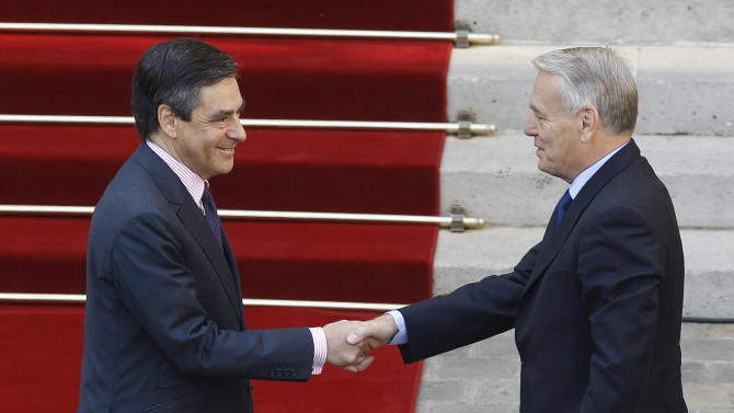 Outgoing French prime minister Francois Fillon, left, greets new prime minister Jean-Marc Ayrault, right, at the Hotel Matignon in Paris, Wednesday May 16, 2012. France's new prime minister, a moderate Socialist with an affinity for Germany who will no doubt be quickly pressed into service to tend to the nation's all-important relationship with Berlin, took office Wednesday.(AP Photo/Remy de la Mauviniere)
