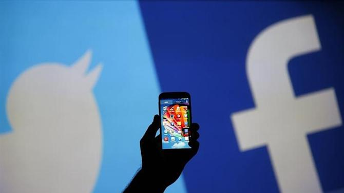 A man holds up a Samsung S4 smartphone against a video screen with Twitter and Facebook logos in this photo illustration taken in the central Bosnian town of Zenica, August 14, 2013. REUTERS/Dado Ruvic