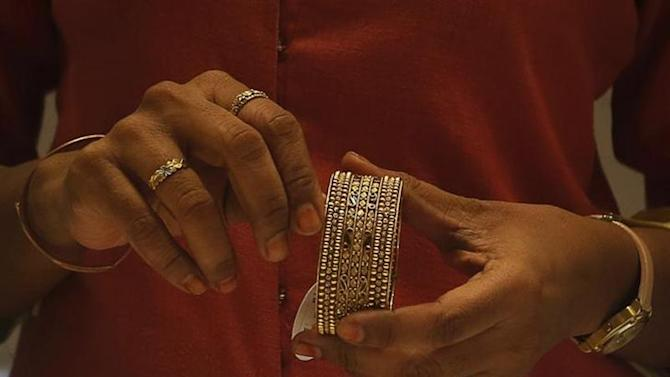 An employee shows a gold bangle to a customer inside a jewellery showroom in Mumbai August 30, 2013.
