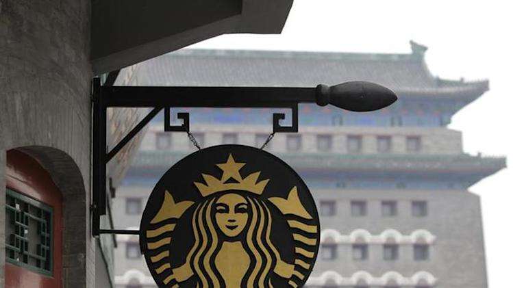 The Starbucks logo is seen outside its coffee store in front of Zhengyangmen Gate at Qianmen Commercial Street in central Beijing, April 19, 2012. REUTERS/Jason Lee/Files