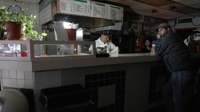 FILE - In this Wed., Oct. 31, 2012 file photo, Leigh Dworkin, right, waits for a slice of pizza as Carlos Quizhplema, left, and Rosa Rosas work behind the counter at Frank's Trattoria, in New York.  The establishment had water, but no electricity or phone service. Quizhplema rode his bicycle 3 hours from the Flushing section in the Queens borough of New York to get to work. (AP Photo/Tina Fineberg, File)