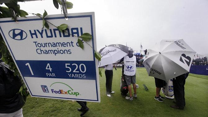 Players and their caddies stand under umbrellas as they wait to tee off in the first round at the Tournament of Champions golf tournament on Friday, Jan. 4, 2013, in Kapalua, Hawaii. (AP Photo/Elaine Thompson)