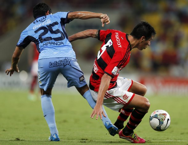 Victor Caceres (R) of Brazil's Flamengo is tackled by Damir Miranda of Bolivia's Bolivar during their Copa Libertadores soccer match at Maracana stadium in Rio de Janeiro March 12, 2014. REUTERS/Sergio Moraes (BRAZIL- Tags: SPORT SOCCER)