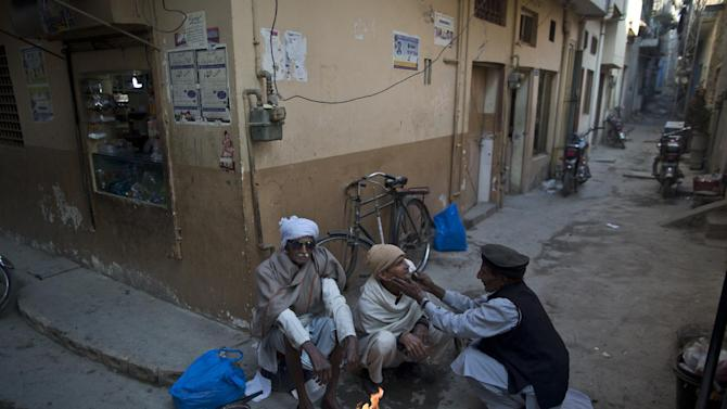 Elderly Pakistani Christian men, sit around a fire to warm from the morning cold, as one of them has his beard shaved by a street barber, before heading to an outdoor Mass on Christmas Day, in a Christian neighborhood in Islamabad, Pakistan, Thursday, Dec. 25, 2014. (AP Photo/Muhammed Muheisen)