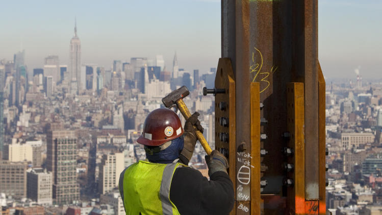 "FILE- In this Dec. 16, 2010, file photo, an ironworker connects a steel plate to a column at One World Trade Center in New York. The Empire State Building is visible in the rear upper left. One World Trade Center, the giant monolith being built to replace the twin towers destroyed in the Sept. 11 attacks, will lay claim to the title of New York City's tallest skyscraper on Monday, April 30, 2012, as workers erect steel columns that will make its unfinished skeleton a little over 1,250 feet, just high enough to peak over the observation deck on the Empire State Building. The milestone is a preliminary one. The so-called ""Freedom Tower"" isn't expected to reach its full height for at least another year, at which point it is likely to be declared the tallest building in the U.S.  (AP Photo/Mark Lennihan, File)"
