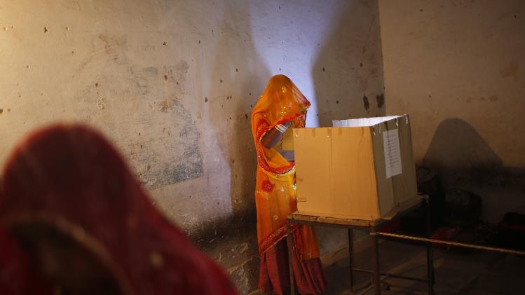 A woman casts her vote at a polling station in Ajmer district in the desert Indian state of Rajasthan