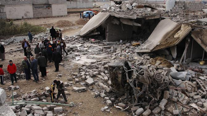 People inspect the scene of a car bomb attack in al-Mouafaqiyah, a village inhabited by families from the Shabak ethnic group, near the city of Mosul, 225 miles (360 kilometers) northwest of Baghdad, Iraq, Monday, Dec. 17, 2012. Three car bomb explosions in Iraq's north on Monday, killing and wounding scores of people, police said. (AP Photo)