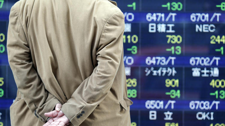 A man looks at an electronic stock board of a securities firm in Tokyo, Friday, March 22, 2013.  Japanese stocks tumbled Friday as investors were disappointed by a lack of specifics from the new central bank chief on boosting the economy while other Asian markets fluctuated because of uncertainty over Cyprus' troubled bank restructuring. (AP Photo/Koji Sasahara)