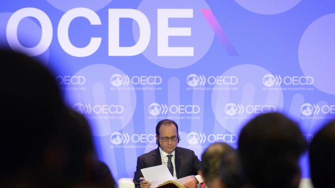"French President Hollande reads notes before delivering his speech on ""Investment and Climate"" during the OECD Ministerial Council meeting at the OECD headquarters in Paris"