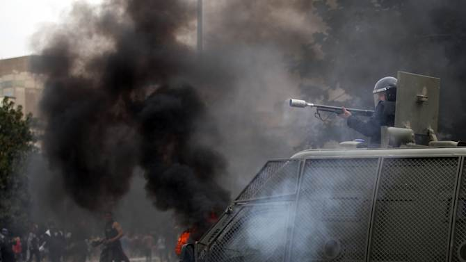 Egyptian protesters clash with riot police near Tahrir Square, Cairo, Egypt, Monday, Jan. 28, 2013. Health and security officials say a protester has been killed in clashes between rock-throwing demonstrators and police near Tahrir Square in central Cairo. The officials say the protester died Monday on the way to the hospital after being shot. (AP Photo/Khalil Hamra)
