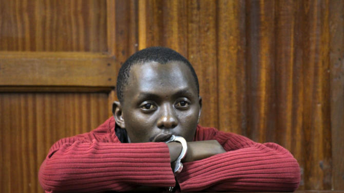 Suspect Elgiva Bwire Oliacha, 28, appears in court to face charges related to the twin grenade blasts which took place on Monday, in Nairobi, Kenya Wednesday, Oct. 26, 2011. The Kenyan suspect arrested after two grenade blasts rattled Nairobi this week pleaded guilty in court to nine charges, including causing grievous bodily harm to two people during Monday evening's blast at a bus stop, and said that he is a member of the al-Qaida-linked Somali militant group al-Shabab. (AP Photo/Khalil Senosi)