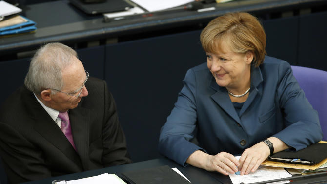 German Chancellor Angela Merkel, right, and German Finance Minister Wolfgang Schaeuble, left, during a meeting of the German federal parliament, Bundestag, in Berlin, Germany, Thursday, April 18, 2013.  The German Parliament has approved a 10 billion-euro (US $13 billion) rescue package for Cyprus by a wide margin.   (AP Photo/Michael Sohn)