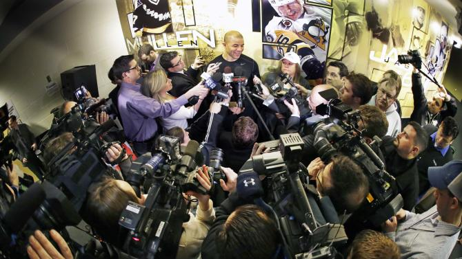 Pittsburgh Penguins' Jarome Iginla, top center, meets the media outside the Penguins locker room before an NHL hockey game against the New York Islanders in Pittsburgh Saturday, March 30, 2013. (AP Photo/Gene  J. Puskar)