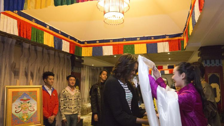 U.S. first lady Michelle Obama, center, receives a Tibetan scarf as she and her daughters Sasha, Malia, and mother Marian Robinson arrive to a Tibetan restaurant for lunch in Chengdu in southwest China's Sichuan province Wednesday, March 26, 2014. (AP Photo/Andy Wong, Pool)
