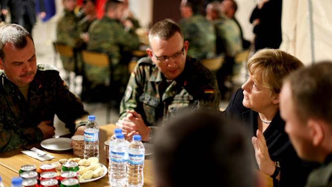 German Chancellor Angela Merkel , second right, talks to unidentified  German soldiers in Kahramanmaras, Turkey, Sunday Feb. 24, 2013.   German Chancellor Angela Merkel is visiting German troops deployed to operate Patriot missile batteries in Turkey. The Patriots were sent to Turkey, a NATO member, to protect it from spillover from Syria's civil war. Merkel's two-day visit comes as Turkey grows increasingly frustrated over the slow progress in its bid for European Union membership. Before arriving Sunday, Merkel said she backs opening a new chapter in those stalled talks, despite being skeptical about Turkey's accession.  The chancellor's first stop was Kahramanmaras, some 100 kilometers (60 miles) from the Syrian border, where some 300 German troops are manning two out of six NATO-deployed anti-missile batteries.  (AP Photo/dpa,Kay Nietfeld)