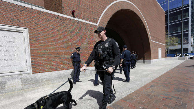 A Department of Homeland Security official walks with a bomb-sniffing dog near the main entrance to federal court, in Boston, Monday, May 6, 2013. A magistrate judge on Monday agreed to release Robel Phillipos, 19, who was charged last week with lying to investigators about visiting Boston Marathon bombing suspect Dzhokhar Tsarnaev's college dorm room after the bombings. (AP Photo/Steven Senne)