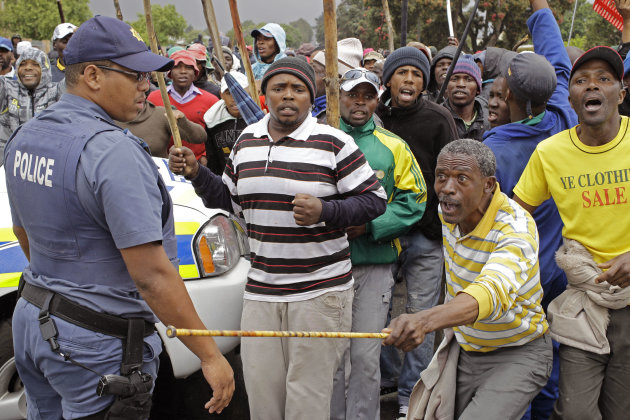 <p>               A South African Policeman, left,  provide security as farm workers demonstrate due to low wages in the town of Grabouw, South Africa, Wednesday, Jan 9, 2013. Striking farm workers on Wednesday set up barricades and threw stones at motorists and police in a South African province whose vineyards are vital to the wine industry, prompting riot officers to close roads and arrest at least 50 demonstrators, South African media reported. (AP Photo/Schalk van Zuydam)