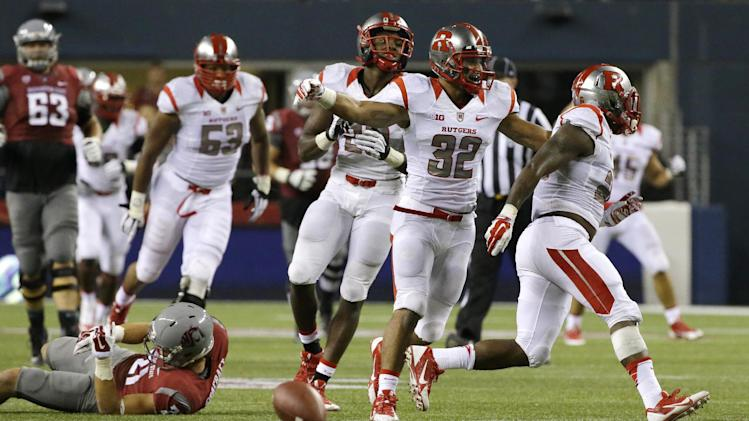 Rutgers defensive players Johnathan Aiken, right, Justin Goodwin (32) and Davon Jacobs, third from right, celebrate after Aiken knocked the ball out of the hands of Washington State wide receiver River Cracraft late in the second half of an NCAA college football game, Thursday, Aug. 28, 2014, in Seattle. Rutgers won 41-38. (AP Photo/Ted S. Warren)