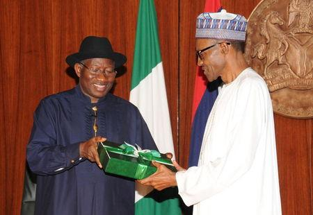 Nigeria's President Goodluck Jonathan (L) presents a gift to president-elect Muhammadu Buhari at the presidential villa in Abuja