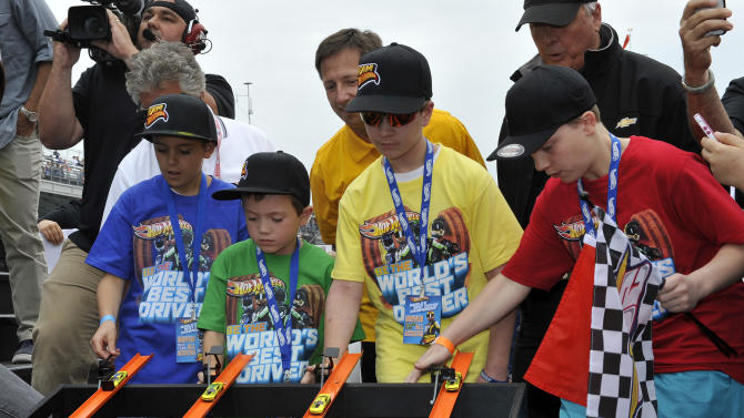 """IMAGE DISTRIBUTED FOR HOT WHEELS - From left,  Tucker Weisman, Alex Bartlett, Samson Poniatowski and Christopher Bienusa kick off the Hot Wheels """"World's Best Driver Championship"""" on the front straightaway of the Indianapolis Motor Speedway on Saturday, May 25, 2013. Hot Wheels created a world record-setting one mile-long toy track. (Photo by Phil Abbott/Invision for Hot Wheels/AP Images)"""