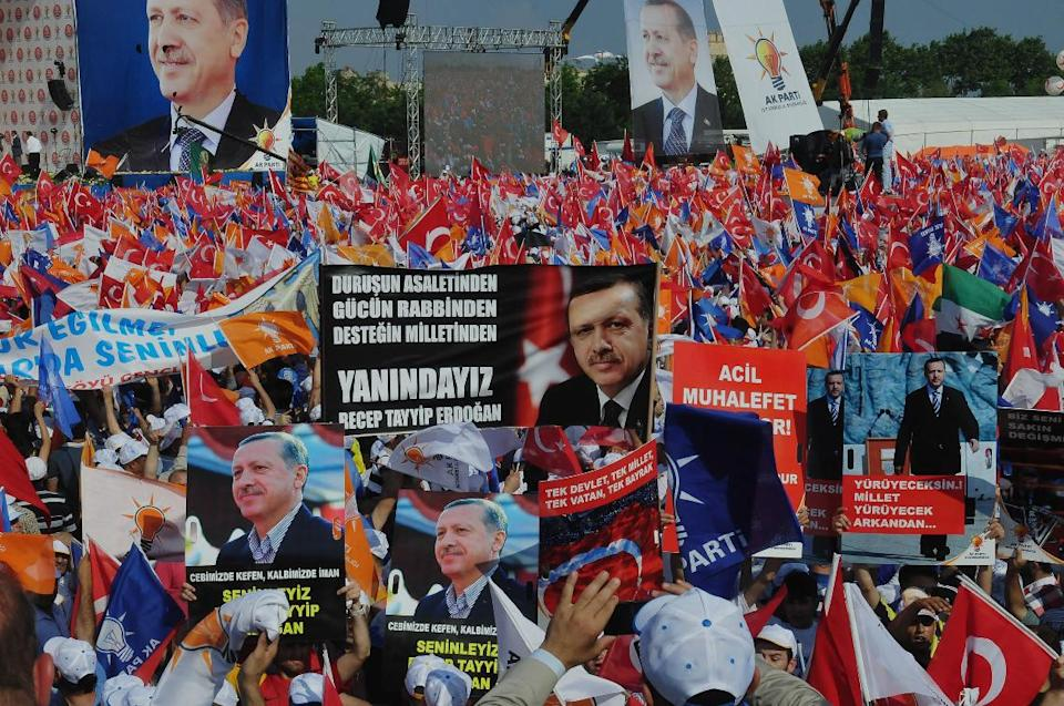 Supporters of Turkish Prime Minister Recep Tayyip Erdogan wave his posters before he arrives to address a party rally in Istanbul, Turkey, Sunday, June 16, 2013.The banner at the center reads: 'We are with you.' (AP Photo/Burhan Ozbilici)