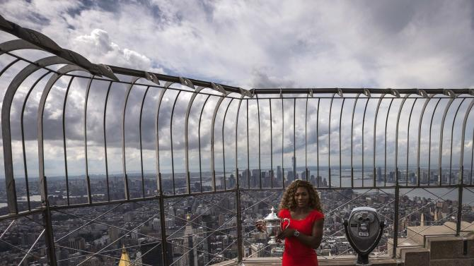Serena Williams of the U.S. holds her U.S. Open tennis tournament trophy from atop the Empire State Building in New York