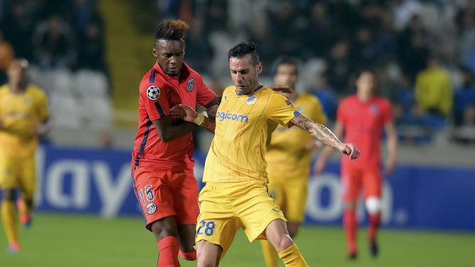APOEL Nicosia's Sergio is challenged by Paris Saint-Germain's Bahebeck during their Champions League Group F soccer match at GSP  Stadium in Nicosia
