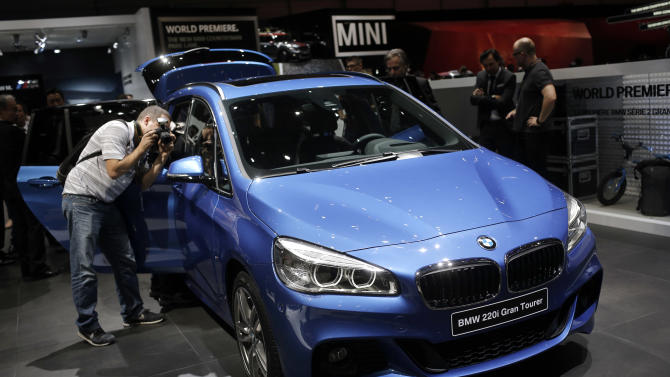 Journalists take pictures of the BMW 220i Gran Tourer   during the first press day of the Geneva International Motor Show Tuesday, March 3, 2015 in Geneva, Switzerland. The show opens its doors to the public March 5 through March 15. (AP Photo/Laurent Cipriani)