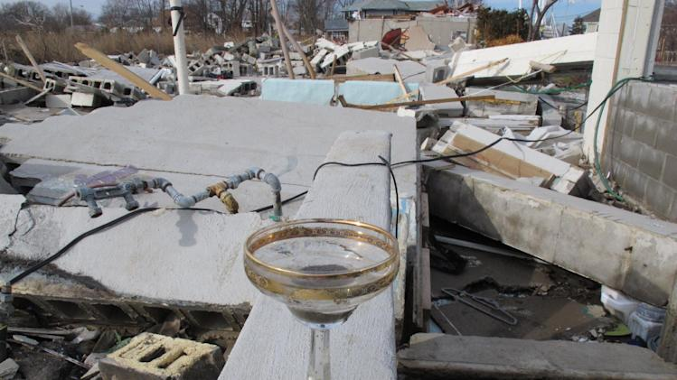 A champagne glass sits atop the foundation of a storm-ruined house in Union Beach N.J. on Dec. 12, 2012. An artificial Christmas tree fished from the gutter after the storm has become a rallying point in a depressing holiday season like no other for Union Beach, whose residents have decorated it. (AP Photo/Wayne Parry)