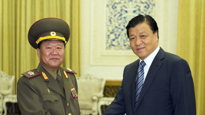 In this May 23, 2013 photo released by China's Xinhua News Agency, Liu Yunshan, right, a member of the Standing Committee of the Political Bureau of the Communist Party of China (CPC) Central Committee, meets with North Korean envoy Choe Ryong Hae in Beijing, China. On a visit to repair ties with China and waiting to meet its leader, Choe paid deference Thursday to hopes by the North's chief ally for renewed multinational nuclear talks. (AP Photo/Xinhua, Xie Huanchi) NO SALES