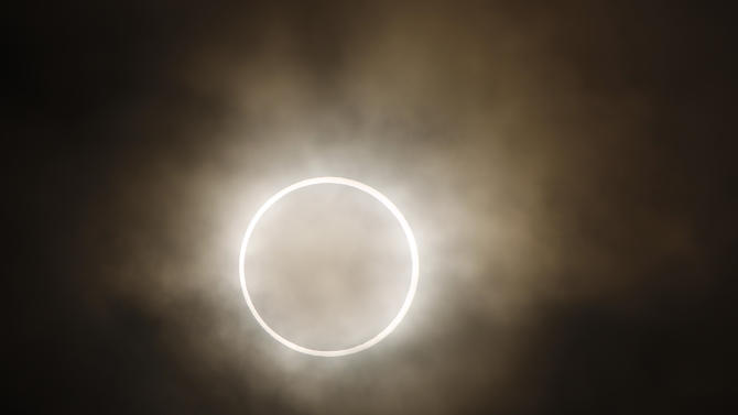 """The moon slides across the sun, showing a blazing halo of light,  during an annular eclipse at a waterfront park in Yokohama, near Tokyo, Monday, May 21, 2012. Millions of Asians watched as a rare """"ring of fire"""" eclipse crossed their skies early Monday. The annular eclipse, in which the moon passes in front of the sun leaving only a golden ring around its edges, was visible to wide areas across the continent.  (AP Photo/Shuji Kajiyama)"""