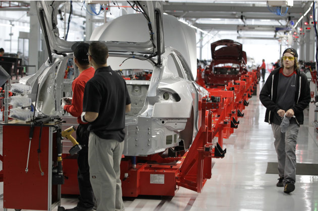 Assembly workers put together a Tesla Model S at the Tesla factory in Fremont, Calif., Friday, June 22, 2012. The first Model S sedan car will be rolling off the assembly line on Friday.  (AP Photo/Pa