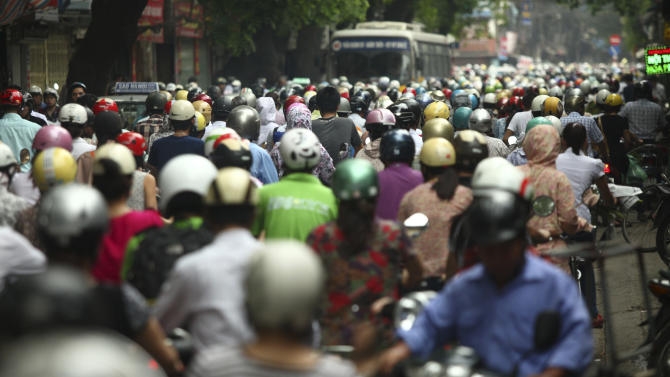 In this photo taken Monday, May 21, 2012, motorcyclists drive in rush hour on La Thanh street which is one of the worst traffic jam roads, in Hanoi, Vietnam. The project of expanding the street is delayed for years due to the disagreement of compensation rates that the government offered to the residents. Experts and officials say inadequate roading and public transport in Hanoi and other Vietnamese cities blocks the social and economic progress of the country where widespread poverty persists despite fast growth in recent years. As construction of Hanoi's inner ring road remains stalled, its traffic will almost certainly worsen in the coming decade. (AP Photo/Na Son Nguyen)