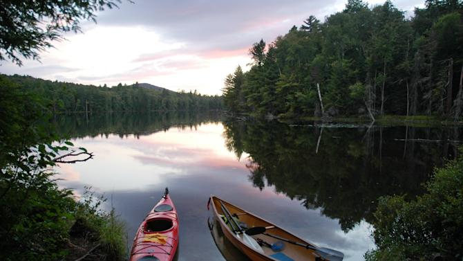 """In this Aug. 20, 2012 photo, a kayak and solo canoe rest at a campsite on East Pine Pond in the Saranac Lakes Wild Forest at Saranac Lake, N.Y.  A new guidebook, """"Adirondack Paddling: 60 Great Flatwater Adventures,"""" is due out this year, aimed at the growing number of people exploring the expanding opportunities for paddlers in the Adirondack Park. (AP Photo/Mary Esch)"""